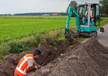 trench: Ground engineering works in the Netherlands. Man and mini excavator dig a trench to lay cables in the village of Wouw, North-Brabant, Netherlands on September 15, 2011.