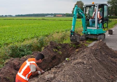 Ground waterbouwkundige werken in Nederland. Man en mini-graafmachine graaft een geul leggen van kabels in het dorp Wouw, Noord-Brabant, Nederland op 15 september 2011.