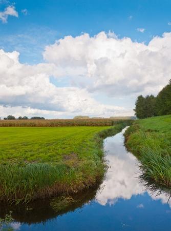 Una zanja nublada. Maravilloso cielo reflejada en una pequeña zanja de holandés