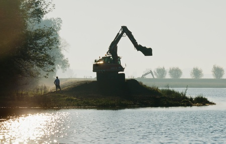 dikes: Working on Dutch dikes in the early morning sun Editorial