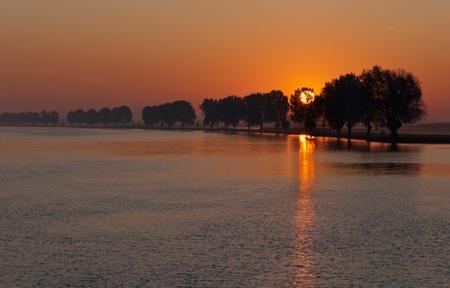 Zonsopgang bij de Nederlandse rivier de Bergse Maas in de buurt van het dorp Raamsdonksveer, Noord-Brabant6 Stockfoto - 10756712