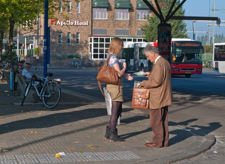 Jehovah s Witness in conversation with a woman waiting in front of the railway  station, Breda, Netherlands, October 2, 2011