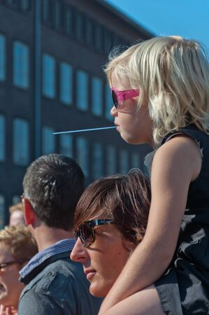 Girl with a straw in her mouth also looks at the runners during the yearly Canal Run 2011, Breda, Netherlands, October 2, 2011 Stock Photo - 10753093