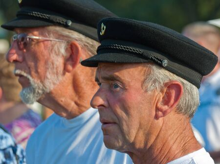 occurrence: Two unidentified members of a skippers choir in the crowd listening to the occurrence of another choir, Biesbosch Regional Festival, Made, North-Brabant, Netherlands, October 2, 2011