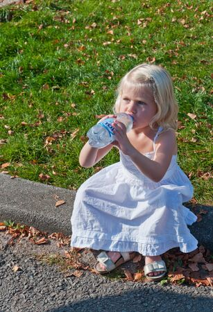 Little blonde girl drinking water sitting on a curb during the yearly Canal Run 2011, Breda, Netherlands, October 2, 2011 Stock Photo - 10793293
