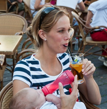 Woman and her baby drinking on a terrace during the yearly Canal Run 2011, Breda, Netherlands, October 2, 2011 Stock Photo - 10807689