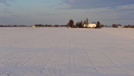 Fields covered with snow in the late afternoon sun in the Netherlands photo