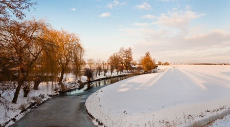 Countryside in the Netherlands with a curved ditch and trees in the afternoon sun Stock Photo - 10893850