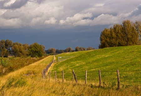 A Dutch dike in sunlight while threatening dark rain clouds arriving Stock Photo - 10977531