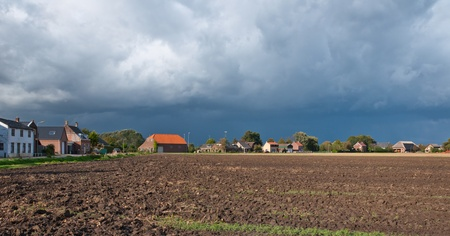 A cloudy sky and a plowed field on the outskirts of a village in the Netherlands Stock Photo - 10977527