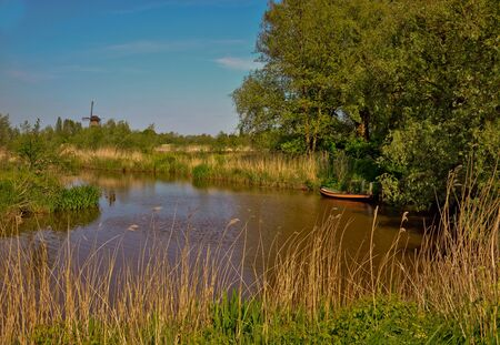 Dutch landscape with a small river with a rowing boat, a windmill and trees photo
