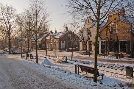 drimmelen: The low sun illuminates a row historic houses in a wintery Dutch village.
