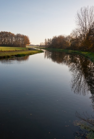 Meandering river in the Netherlands. A very low sun illuminates the landscape. Stock Photo - 11555394