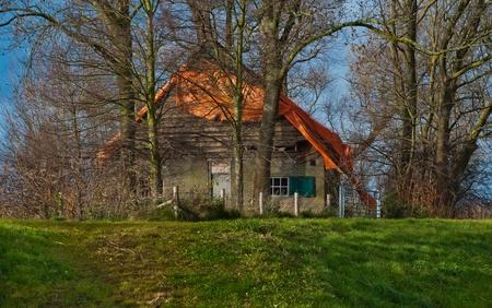 Een Nederlandse dijk in de herfst met een verlaten houten huis
