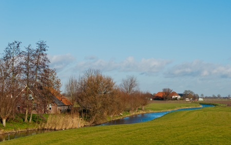 Dutch farms besides a meandering river in fall photo
