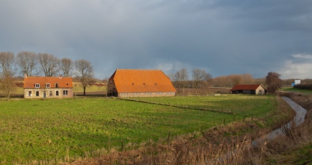 Dutch landscape with an dilapidated and abandoned farm and barn. Winter has begun. photo