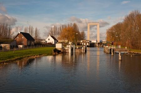 Drawbridge and lock between the rivers Hollands Diep and Roode Vaart near Roodevaart, a hamlet in the Dutch municipality of Moerdijk, Province of North Brabant, in the Netherlands. The bridge provides access to the port and industrial area Moerdijk. Stock Photo - 11768421