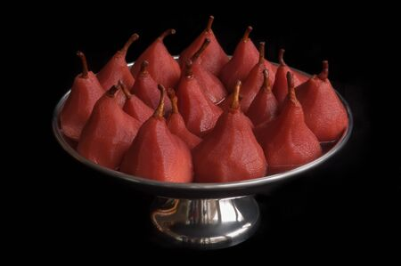 poached: Pears poached in red wine and served in a silver colored bowl Stock Photo