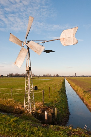 north brabant: Old metal windmill powers a pump to regulate the water level in a Dutch ditch.