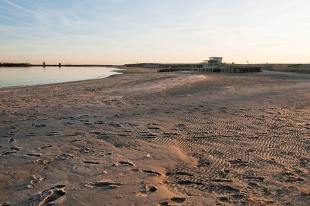 Footprints in the frozen beach at dawn. Overlooking the beach at the Oosterschelde, Zeeland, Netherlands. photo
