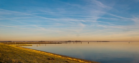 mooring bollards: The lough of the  Oosterschelde (Zeeland, Netherlands) near the dike from South Beveland to North Beveland. It is dawn and the sun is still low.