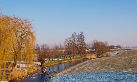 Rural landscape with a curved ditch in the Netherlands. It is winter, some snow has fallen. photo