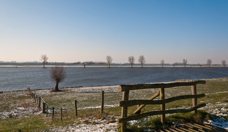 cattle grid: The Dutch river Bergsche Maas in winter. The first snow has fallen. In the foreground a wooden fence and a part of a cattle grid.