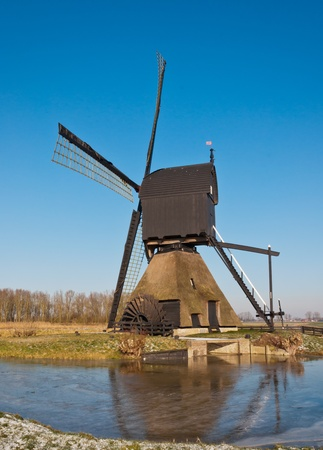 rotational: This windmill Noordeveldse molen in the Dutch village of Dussen is a polder mill from 1795. Until 1964 the mill has been used as a water pump for the low-lying polder. The mill was restored in 1969 and, after a fire in 1992, reestablished in 1997. Stock Photo