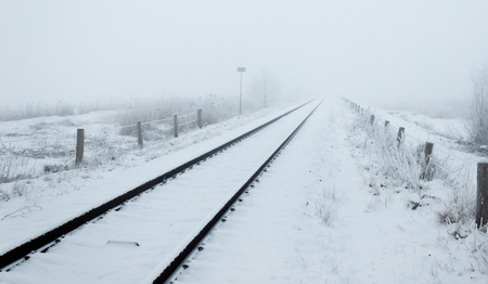 With fresh snow covered railway tracks in the morning mist. It is still early in the morning and the fog has not lifted. A spontaneously generated low key image. Stock Photo - 12307221