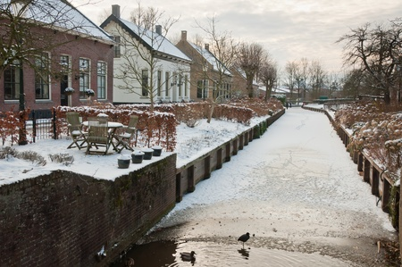 drimmelen: Winter in the historic Dutch village Drimmelen (North Brabant). The canal is almost frozen but the ducks can still swim in the cold water.
