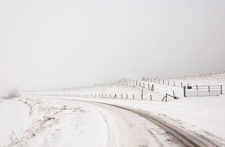 A snowy landscape with a road, fences and a dike. It is very early in the morning and it freezes very much in the Netherlands. The morning mist still hangs over the landscape. The view is limited and less colorful. photo