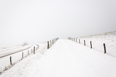 A snowy landscape with roads and  fences. It is very early in the morning and it freezes very much in the Netherlands. The morning mist still hangs over the landscape. The view is limited and less colorful. Stock Photo - 12307230