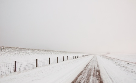 Snowy landscape with a road and a fence. It is very early in the morning and it freezes very much in the Netherlands. The morning mist still hangs over the landscape. The view is limited and less colorful. photo