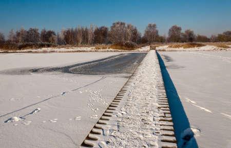 Wooden footbridge over the snowy ice in Dutch nature reserve Dintelse Gorzen  (near the village of Steenbergen, North-Brabant). photo