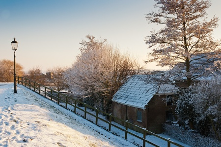 A snowy embankment with a vintage streetlight and a staircase with wooden handrail to the house down to the dike. photo