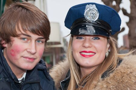 Made, North-Brabant, Netherlands � February 19, 2012 - Carnival Parade, impression of the people, smiling girl with police cap and her boyfriend.