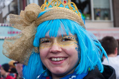 made in netherlands: Made, North-Brabant, Netherlands - Carnival Parade, impression of the people, smiling young woman with a blue wig. Editorial