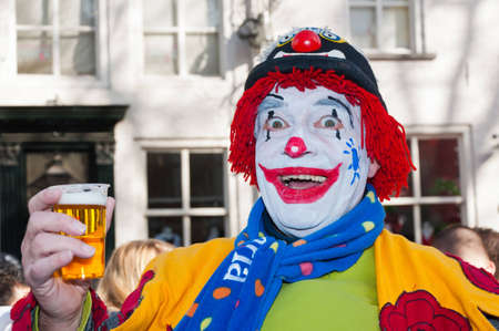 Breda, North-Brabant, Netherlands � February 20, 2012 � Carnival Parade, impression of the people, a colorful painted clown with a glass of beer.