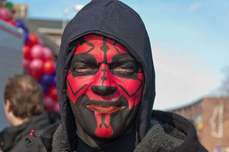 Breda, North-Brabant, Netherlands – February 20, 2012 – Carnival Parade, impression of the people, man with a black hood and a red and black painted face. Stock Photo - 12385684