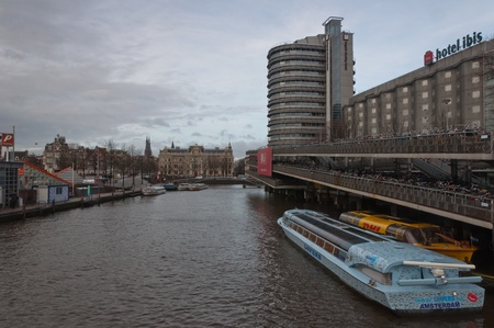 Amsterdam. North-Holland, Netherlands – January 21, 2012 - A view at the canal near the Stationsplein and the Prins Hendrikkade next to the Central Station in Amsterdam (Netherlands). Stock Photo - 12690612
