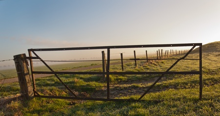 It is still early in the morning  The grass is wet and the dewdrops hang on the rusty gate Stock Photo - 12889391