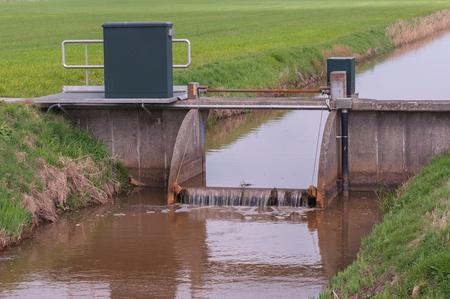 Kleine greppel met een stuw tussen weilanden in Nederland