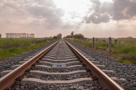 Dutch rural landscape with a long single railway track and concrete sleepers  Sunbeams shine through the cloudy sky Stock Photo - 13546198