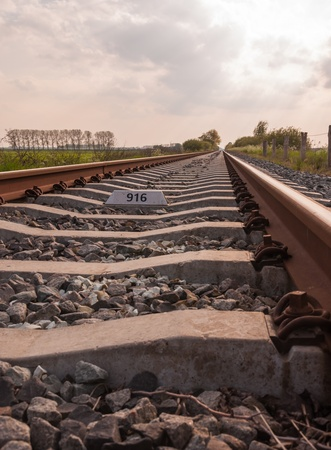 Closeup of a long and single railway track and concrete sleepers in a Dutch rural landscape. Stock Photo - 13546197