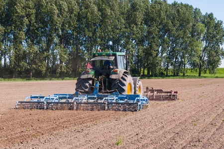drimmelen: Drimmelen, North-Brabant, Netherlands, May 25, 2012, Farmer is killing the weeds by stirring and pulverizing of the soil with a tractor driven cultivator after the crop has begun growing on May 25, 2012 at a field near the Dutch village of Drimmelen. Editorial