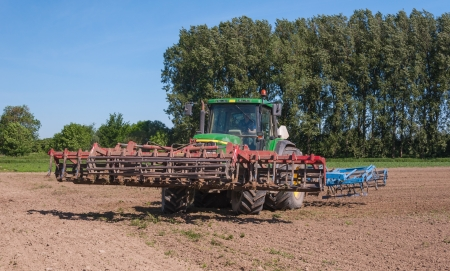 Drimmelen, North-Brabant, Netherlands, May 25, 2012, Farmer is turning the tractor with the attached agricultural machinery on May 25, 2012 at a field near the Dutch village of Drimmelen.