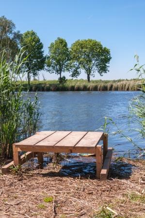 Houten vissen plateau op een natuurlijke vijver in Nederland