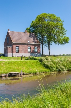 landscape riverside: Romantic house and trees on a Dutch dike next to water  Stock Photo