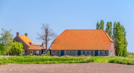 Large farm and barn with orange tiled roofs in the Netherlands.