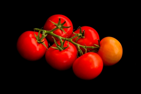 Colorful and tasty truss tomatoes against a black background Stock Photo - 14119914